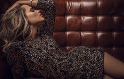 Het jonge sensuele & schoonheidsvrouw stellen op de bank van het luxeleer. Stock Fotografie