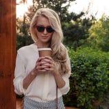 Het jonge sexy blondemeisje die met lang haar in zonnebril een kop van koffie houden heeft in camera en pret en goede stemming di Stock Afbeeldingen