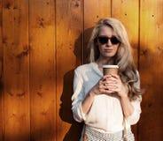 Het jonge sexy blondemeisje die met lang haar in zonnebril een kop van koffie houden heeft pret en goede stemming kijkend in came Stock Fotografie
