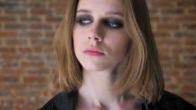 Het jonge sexy droevige meisje met rokerige ogen let op bij camera, het denken concept, baksteenachtergrond stock videobeelden