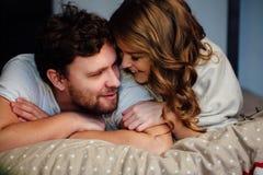 Het jonge sexy paar in liefde die in bed in hotel liggen, die op witte bladen omhelzen, sluit omhoog Stock Foto's