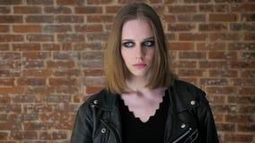 Het jonge sexy vervreemde meisje met rokerige ogen let op bij camera, droefheid, baksteenachtergrond stock video