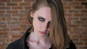 Het jonge sexy zekere meisje met rokerige ogen let op bij camera, baksteenachtergrond stock footage