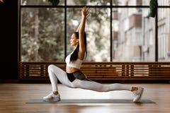 Het jonge slanke donker-haired meisje gekleed in witte sportenbovenkant en legging doet omgekeerde uitvalt en bereikt hoog wapens royalty-vrije stock fotografie