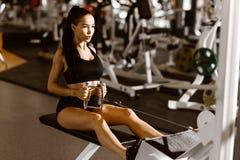 Het jonge slanke donker-haired meisje gekleed in zwarte sportenbovenkant en borrels werkt op de oefeningsmachine uit in de gymnas royalty-vrije stock foto's