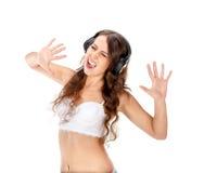 Het jonge slanke donkerbruine meisje luistert muziek in hoofdtelefoons Stock Foto's