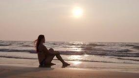 Het jonge slanke meisje in een badpak zit op het strand bij zonsondergang 4K stock video