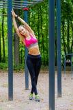 Het jonge slanke portret van vrouwensporten op de opleidingsgrond Stock Foto's