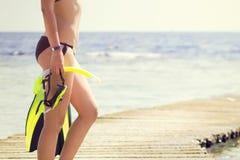 Het jonge snorkelende toestel die van de vrouwenholding het overzees bekijken Royalty-vrije Stock Afbeelding