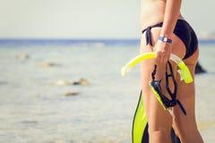 Het jonge snorkelende toestel die van de vrouwenholding het overzees bekijken Stock Afbeelding
