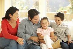 Het jonge Spaanse Familie Ontspannen op Sofa At Home stock afbeelding
