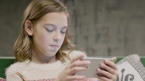 Het jonge spel van het meisjes emotionele spel op de slimme telefoon stock video