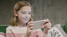 Het jonge spel van het meisjes emotionele spel op de slimme telefoon stock footage