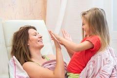 Het jonge spelen in haar handen met een klein meisje stock foto