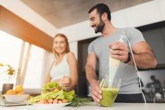 Het jonge sportenpaar treft in de ochtend in de keuken voorbereidingen Een mens maakt een groene plantaardige cocktail stock fotografie