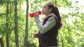 Het jonge sportieve meisje is drinkwater in opleiding Sportman op een looppas in het de zomerpark Langzame Motie stock video