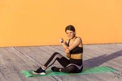 Het jonge sportieve meisje in zwarte sportwear zitting op mat en heeft een sterk gekwetst probleem met elleboog, pijnlijke kramp  stock foto's