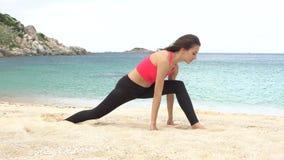 Het jonge sportieve wijfje doet uitrekkende die oefening en zit op streng op het strand dichtbij het overzees wordt verdeeld stock video