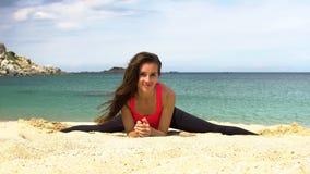 Het jonge sportieve wijfje doet uitrekkende die oefening en zit op strengmidden op het strand dichtbij het overzees wordt verdeel stock videobeelden