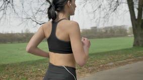 Het jonge sportmeisje loopt met hoofdtelefoons in park in de zomer, gezonde levensstijl, sportconceptie, camera ronde beweging stock videobeelden
