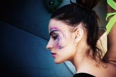 Het jonge stedelijke portret van de finessvrouw met artistieke make-up openluchti Stock Fotografie