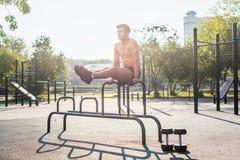Het jonge sterke atleet uitwerken in openluchtgymnastiek, die been opheffende abs doen oefent uit royalty-vrije stock foto's