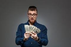Het jonge succesvolle geld van de zakenmanholding over donkere achtergrond De ruimte van het exemplaar Stock Afbeeldingen