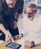 Het jonge team van medewerkers vond een grote het werkoplossing in moderne coworking studio Gebaarde mens die statistiek tonen re Stock Afbeeldingen
