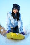 Het jonge tiener sledding onderaan heuvel stock afbeelding