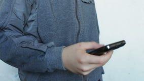 Het jonge tiener spelen op smartphone stock videobeelden