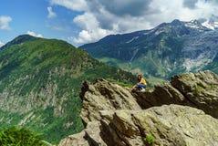 Het jonge tiener stellen op grote steen in Alpen stock foto