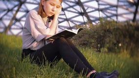 Het jonge tienermeisje in de lezing van de t-shirtlezing neemt nota van zitting op het gras in het park op een zonnige dag stock videobeelden