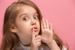 Het jonge tienermeisje die een geheim achter haar fluisteren overhandigt roze achtergrond royalty-vrije stock foto