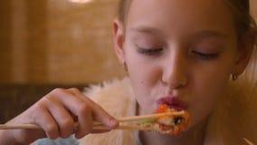 Het jonge tienermeisje die sushi eten rolt met eetstokjes in Japanse koffie dichte omhooggaand stock video