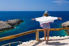 Het jonge tienermeisje geniet van de wind, de zonneschijn en de mening, bij de rand van een hoge klip over het blauwe overzees va royalty-vrije stock fotografie
