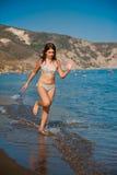 Het jonge tienermeisje spelen met golven bij het strand. Royalty-vrije Stock Foto's