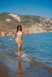 Het jonge tienermeisje spelen met golven bij het strand. Stock Afbeelding
