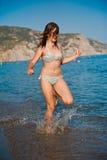 Het jonge tienermeisje spelen met golven bij het strand. Stock Foto's
