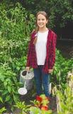 Het jonge tienermeisje stellen met gieter bij tuin Stock Foto's
