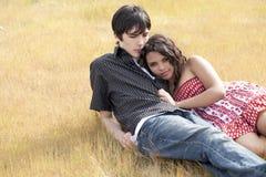 Het jonge tienerpaar doen leunen in geel gras royalty-vrije stock afbeeldingen