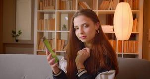 Het jonge tienerwijfje blogger zet app op tablet aan en toont thuis het zijn groene chromascherm en gebaren duim-op stock videobeelden
