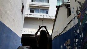 Het jonge toeristenmeisje gaat onderaan de steeg met graffiti op de muren en de einden een foto op haar smartphone nemen stock videobeelden
