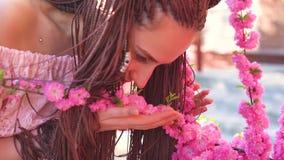 Het jonge toevallige geklede meisje in sakura van glazengeuren bloeit en glimlacht in de camera Nadruk op het concept van de gezi stock video