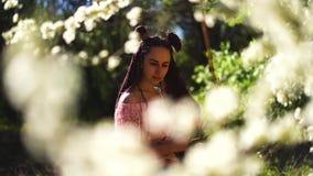 Het jonge toevallige geklede meisje in sakura van glazengeuren bloeit en glimlacht in de camera Nadruk op het concept van de gezi stock footage