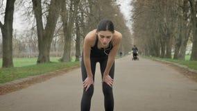 Het jonge uitgeputte sportmeisje rust na dwars, gezonde levensstijl, sportconceptie stock video