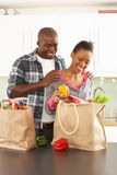 Het jonge Uitpakken die van het Paar in Keuken winkelt Stock Afbeelding