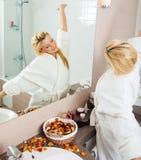 Het jonge uitrekken van de Vrouw zich voor een spiegel Stock Foto's