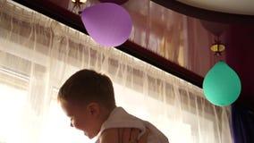 Het jonge vader spelen met baby, die hem in mijn wapens, worp tegenhouden Zonstralen door het venster Gelach en vreugde van stock videobeelden