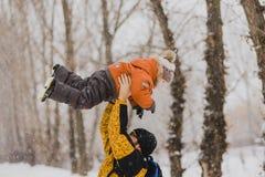 Het jonge vader spelen met zijn baby in een sneeuwpark stock fotografie