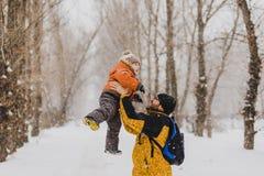Het jonge vader spelen met zijn baby in een sneeuwpark royalty-vrije stock foto